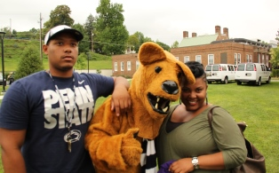 Michael Phelps Jr., 18, and his mother, April Bumbrey, are welcomed at Penn State Schuylkill by the mascot, the Nittany Lion.